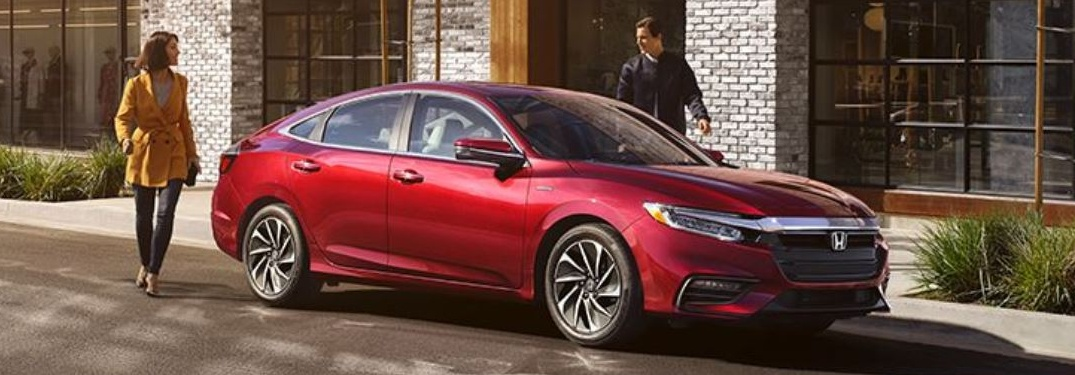 Couple walking beside red 2019 Honda Insight