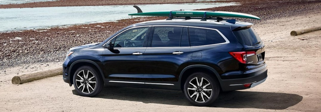 2019 Honda Pilot at a beach with a surfboard