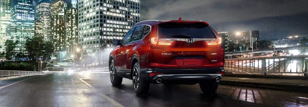 Rear view of the 2019 Honda CR-V driving on city street at night