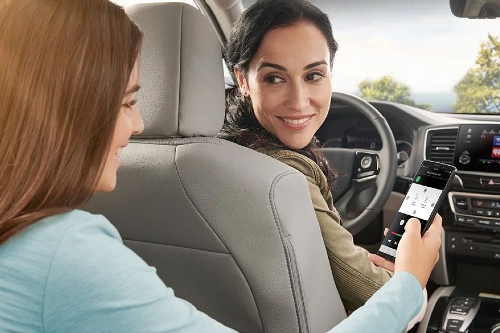 Girl using phone and showing mom in a 2020 Honda Pilot