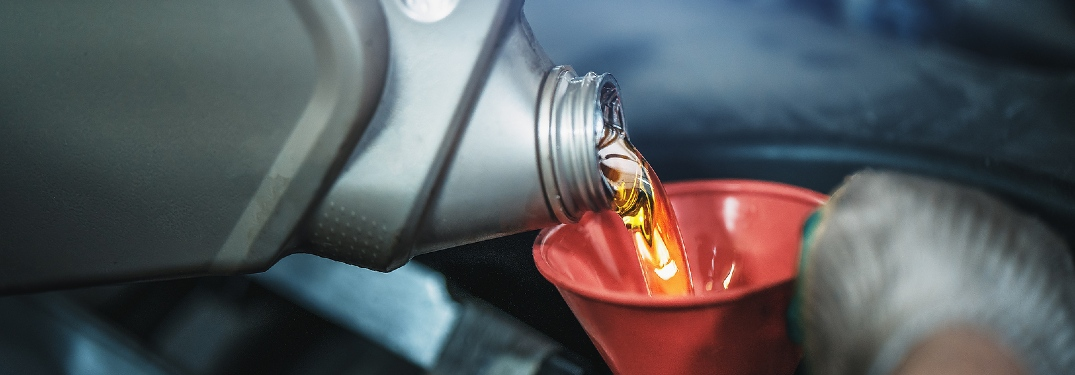 pouring oil into a funnel