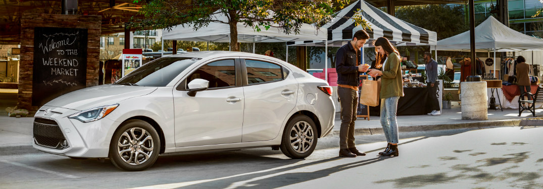 Man and woman standing beside a white 2019 Toyota Yaris