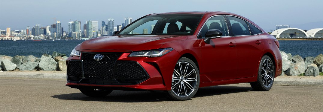 Red 2019 Toyota Avalon parked in front of city skyline