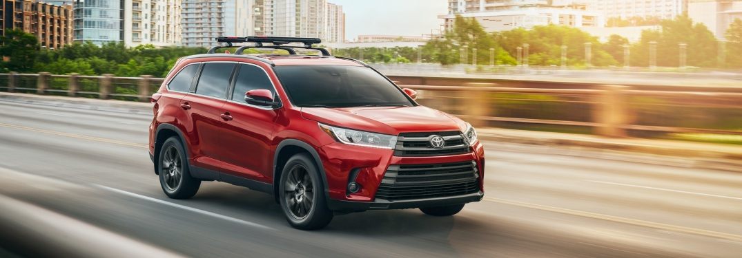 Red 2019 Toyota Highlander driving on highway