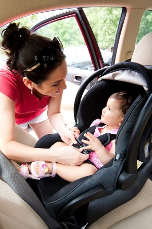 Woman putting her daughter in a car safety seat