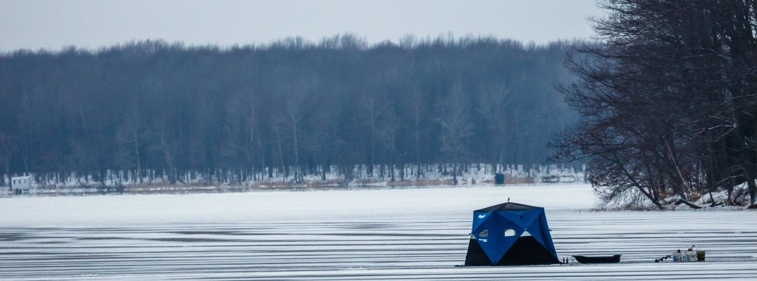An ice fishing tent sitting on an ice-covered lake
