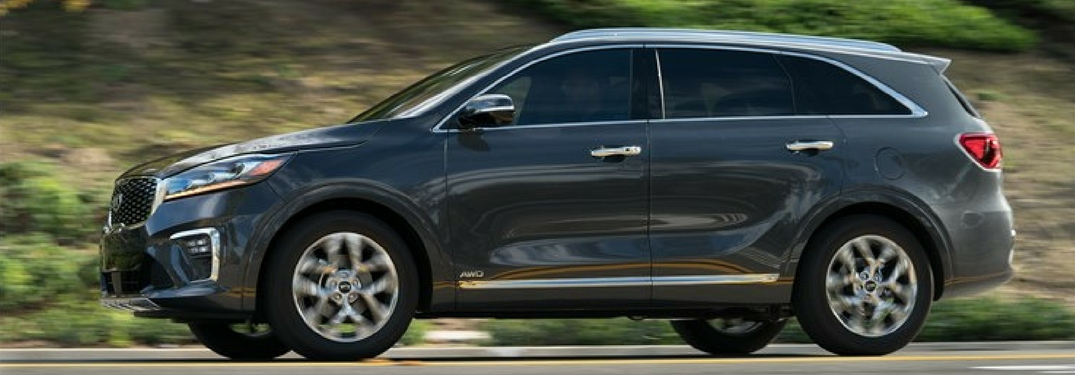 Side profile of the 2019 Kia Sorento driving on a highway near greenery
