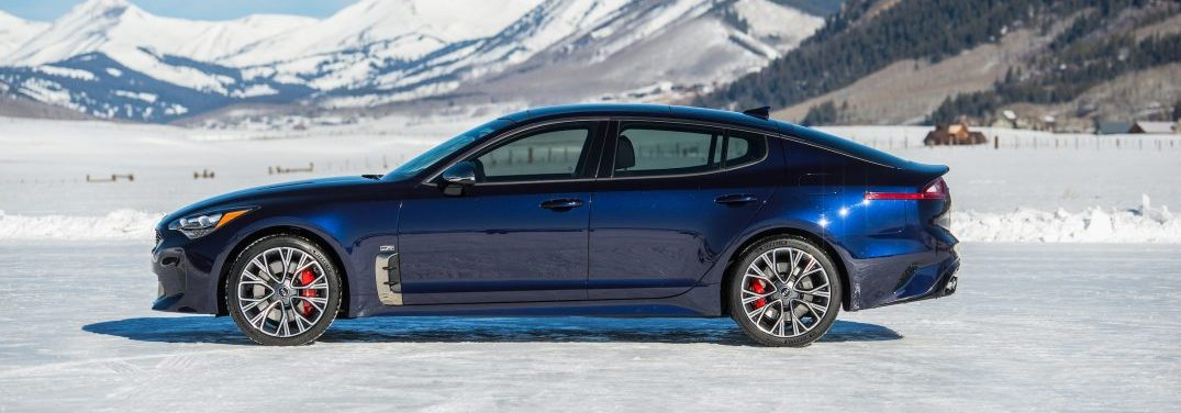 Side profile view of the 2019 Kia Stinger GT Atlantic parked on a snowy field in front of a mountain range