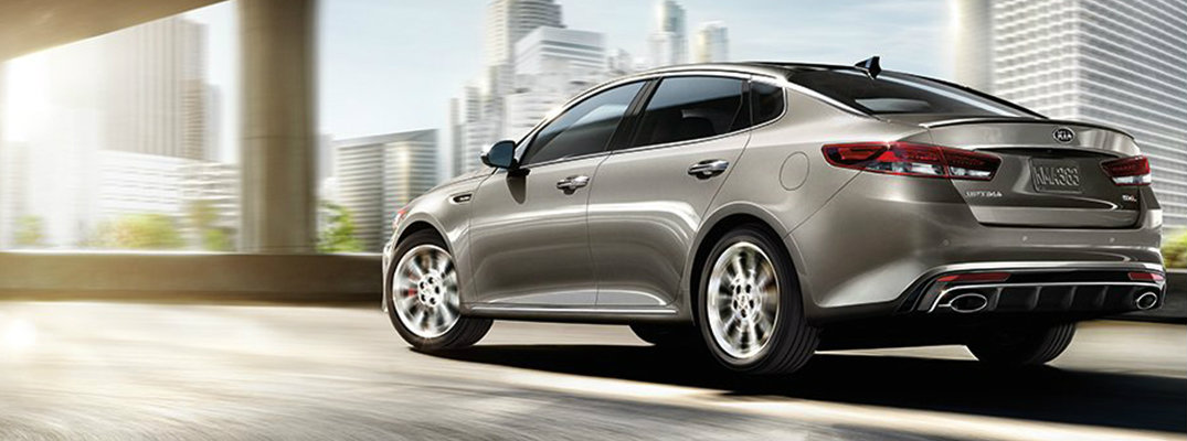 Profile view of pewter 2018 Kia Optima driving on highway ramp