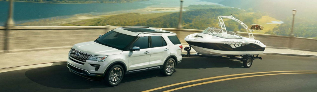 White 2018 Ford Explorer Towing a Boat near a River