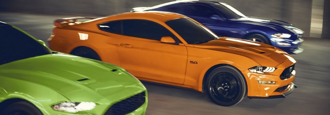 2020 Ford Mustangs driving together on road