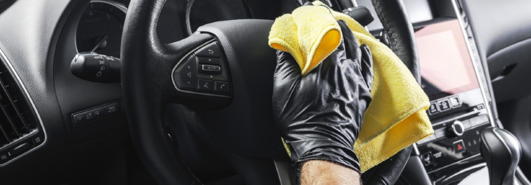 a gloved hand wiping a steering wheel