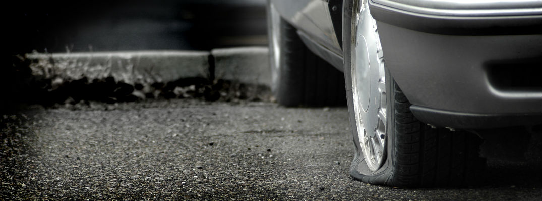 A close up photo of a car's flat tire on blacktop
