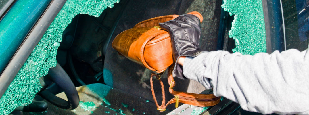 A stock photo of a broken car window with a hand removing a woman's purse