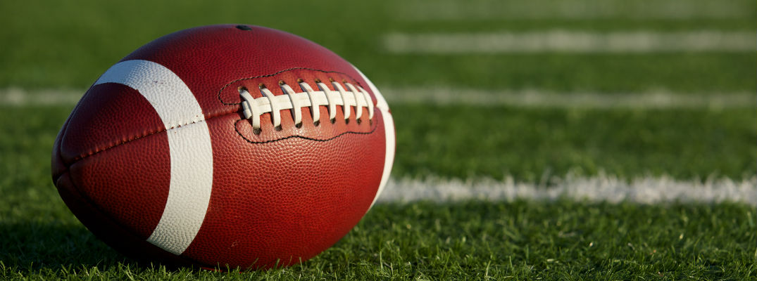 A close up stock photo of a football resting on a field