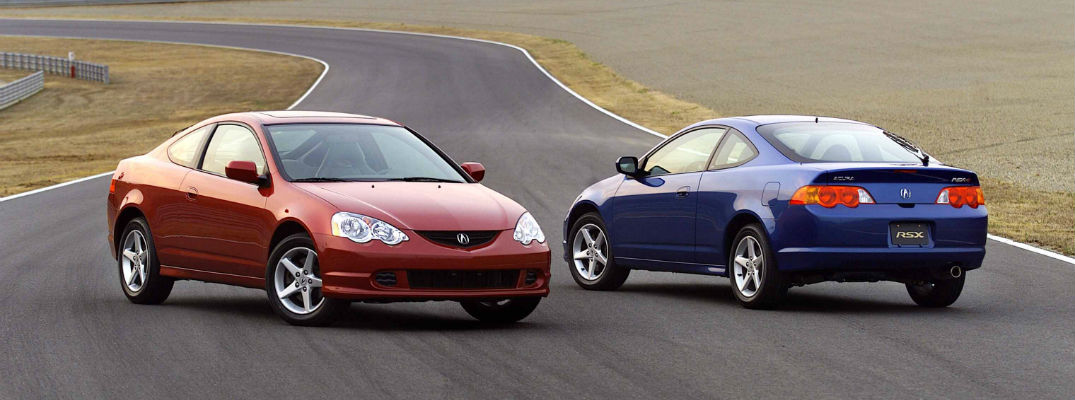 A pair of Acura Type-S coupes parked nose-to-tail on a racetrack.