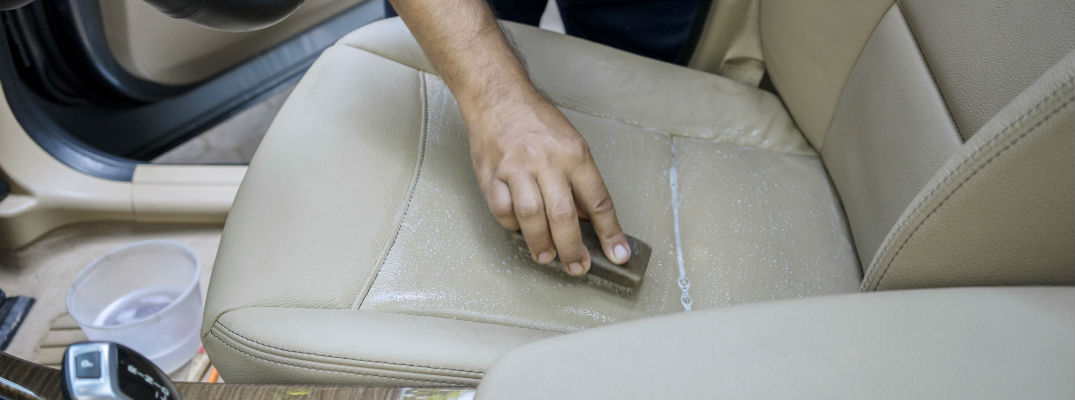 A stock photo of a person scrubbing dirt off of the seat of a car.