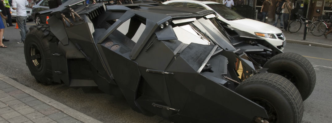 A stock photo of the Bat-Mobile parked on a street.