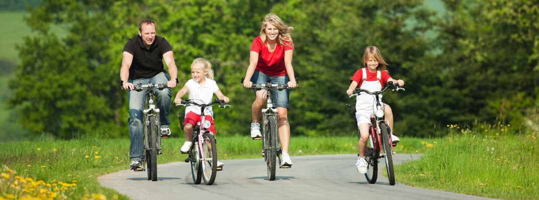 A stock photo of a family riding their bikes on a trail.