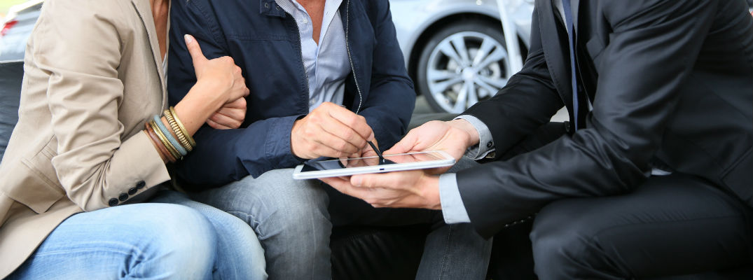 A stock photo of people signing paperwork at a car dealership.