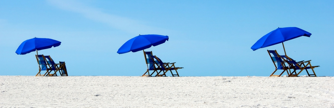 Empty beach chairs in the sand with blue umbrellas