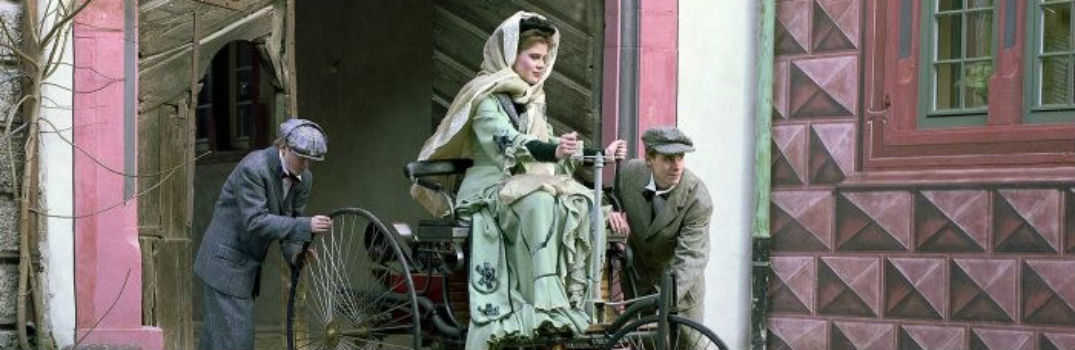 painting of Bertha Benz being pushed in an automobile by her two sons