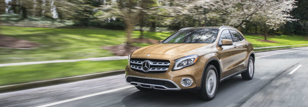 front view of gold mercedes-benz gla 250 driving on street with trees