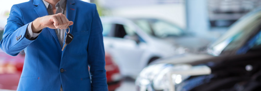 man in blue suit holding car keys in showroom