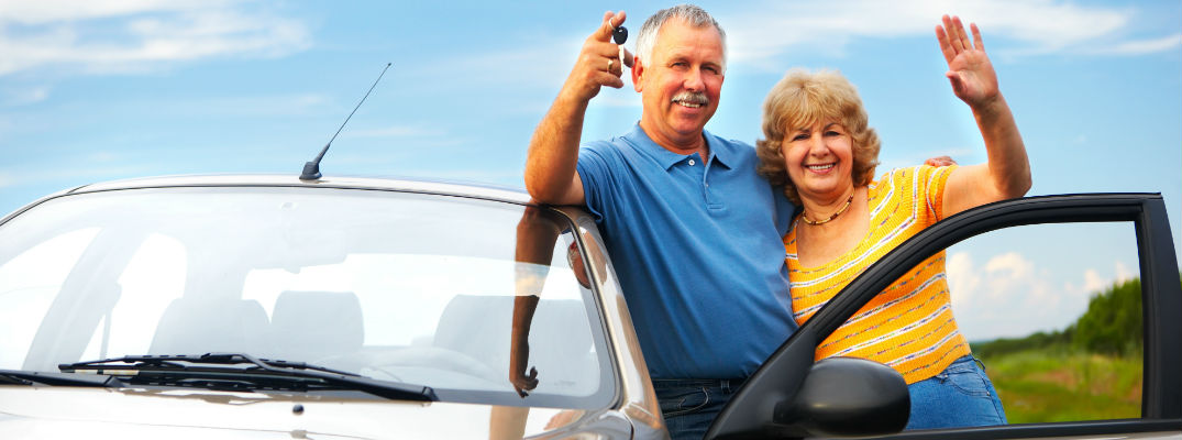 Couple waving with new car