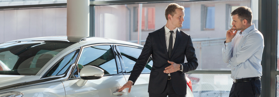 two men look at cars in a showroom