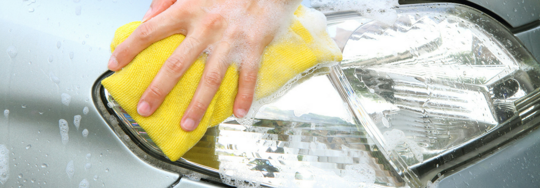 Man cleans headlight with towel