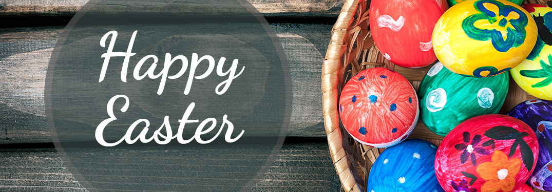 Happy Easter text next to a bowl of colored Easter eggs on wooden planks