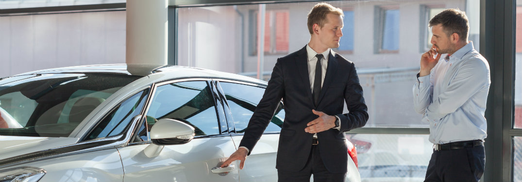 salesman showing off a car to a customer