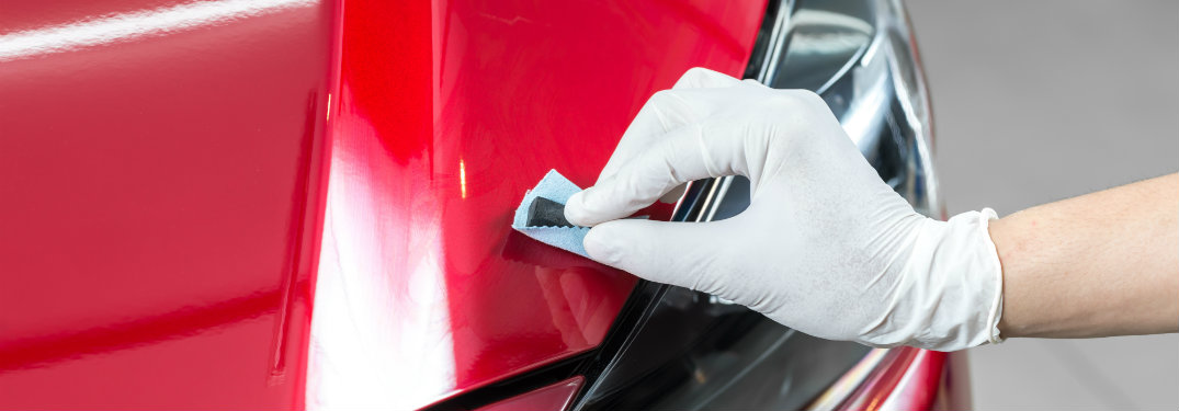 gloved hand polishing a car