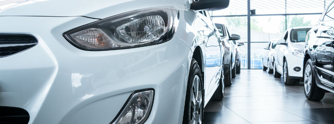A stock photo of vehicles in a dealership's showroom.