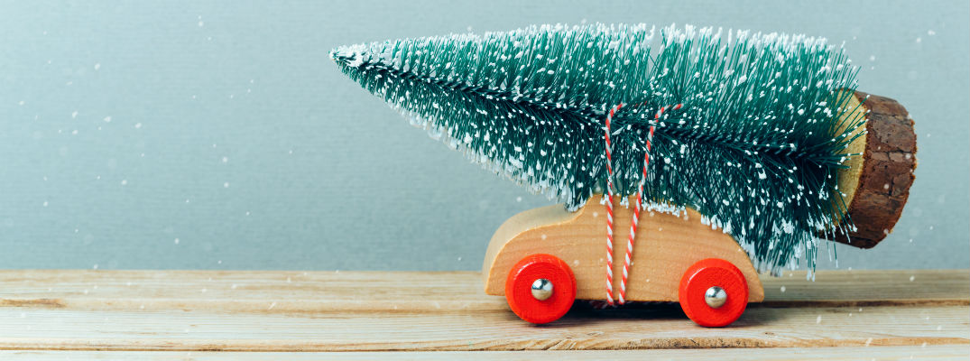 A stock photo with a toy car holding a Christmas tree on a snowy background.