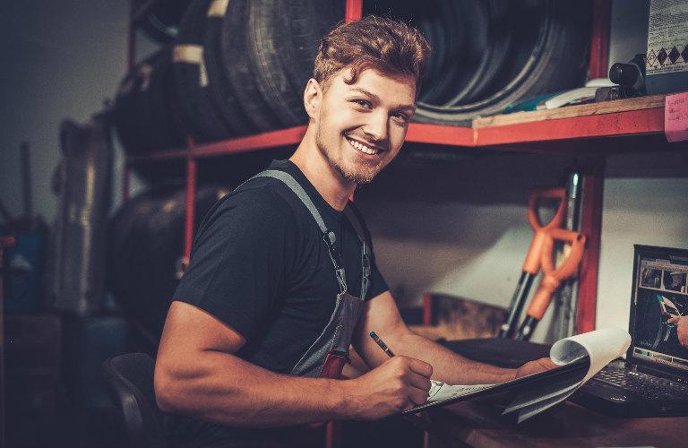 mechanic in shop doing paperwork and smiling at camera