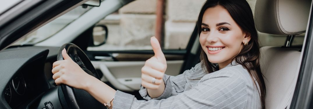 young woman sitting in car and smiling at camera while giving thumbs up gesture