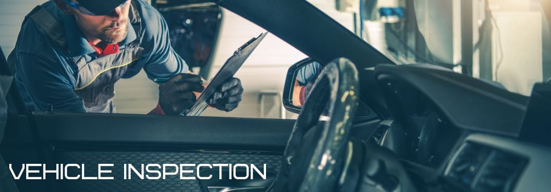 mechanic inspecting inside of a car with the words vehicle inspection overlaid