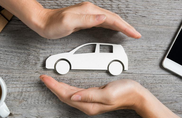 hands covering paper cutout car