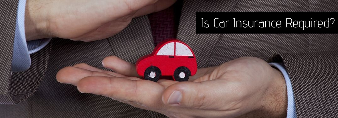 business man hands covering and holding toy car with is car insurance required text