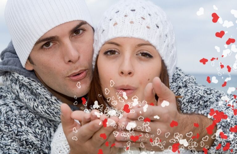 young couple dressed up in winter clothes blowing kisses toward camera that turn into floating hearts