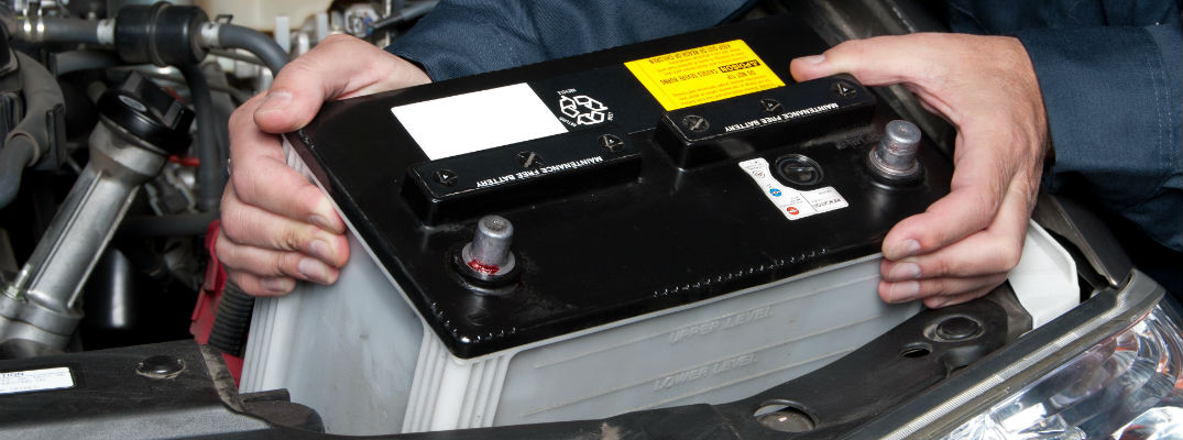 Hands of an auto mechanic placing a new battery in a car