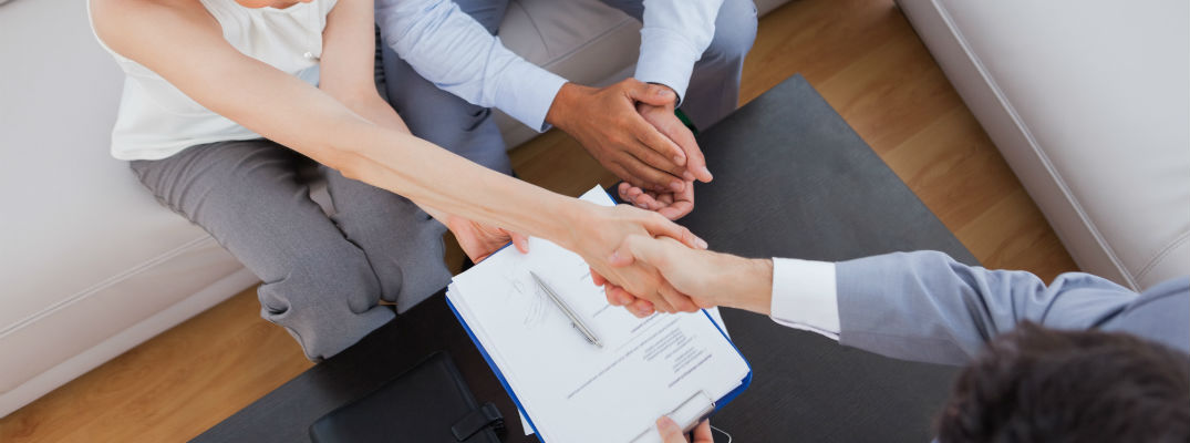 A stock photo of people shaking hands after filling out paperwork