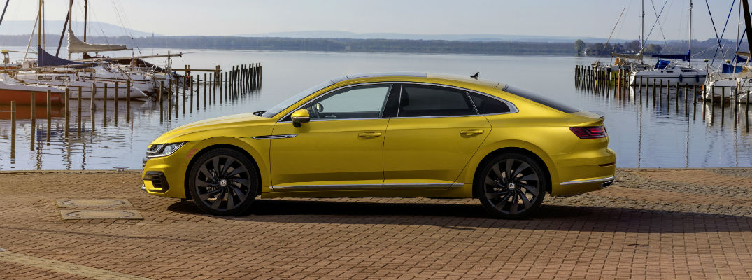 A left profile photo of the 2019 VW Arteon in front of a harbor.