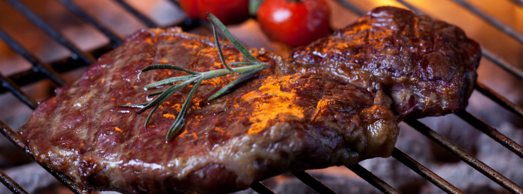 A stock photo of a steak cooking on a grill.