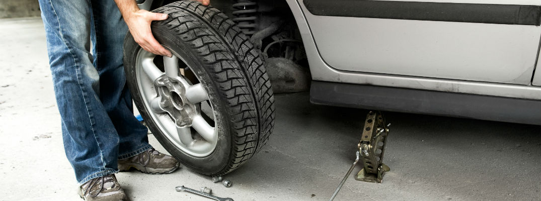 A stock photo of someone changing a tire in a garage.