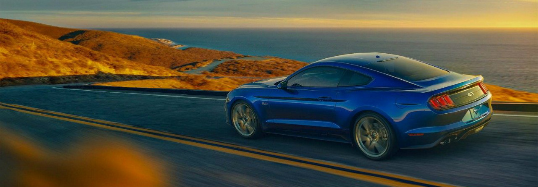 blue 2018 Ford Mustang driving on open road at sunset