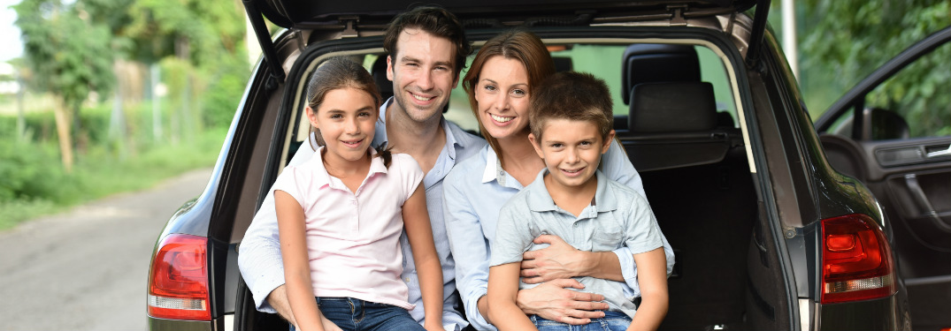 Family of four sitting in the back of their SUV