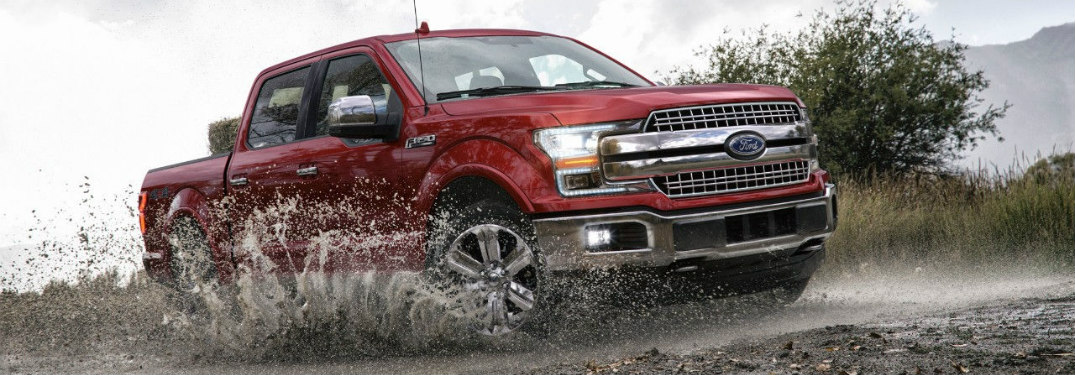 Red 2018 Ford F-150 Raptor driving through muddy water